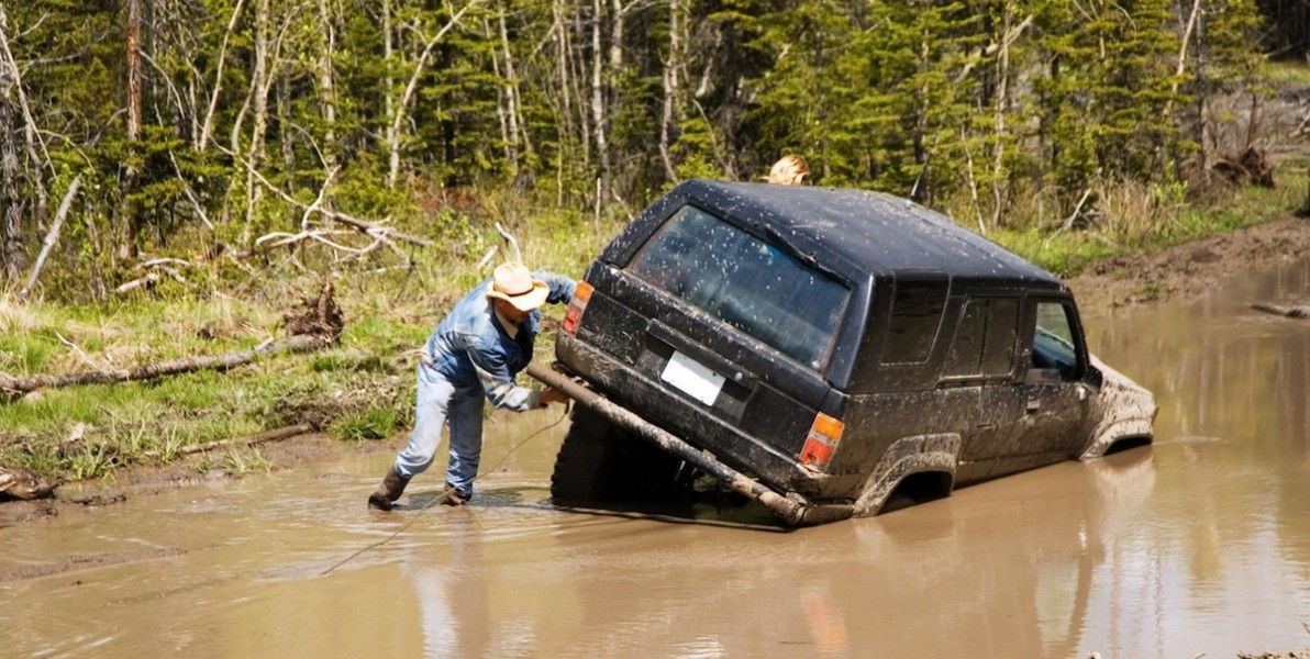 4x4 vehicle stuck in a mud hole, with a man attaching a winch. (c) Kris Butler. Via 123rf.com.