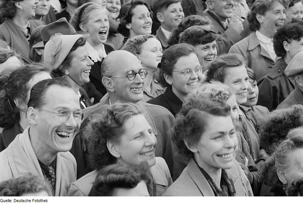 Smiling crowd— Bild Publikum. Photograph by Roger & Renate Rössing , 1954 (CC BY-SA 3.0 DE). Deutsche Fotothek?. Via Wikimedia Commons.