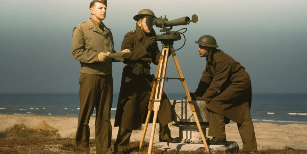 Men of Fort Story operate an azimuth instrument, to measure the angle of splash in sea-target practice. 1942. (reversed)
